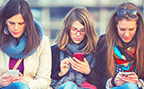 Young women in a row looking at their smart phones