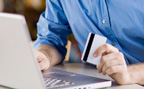 Man holding credit card while using laptop computer